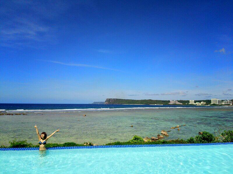 おかっぱミユキが両手を広げて気持ちよさそうに伸びをしている様子。背景にはグアムの青い海が広がっている。