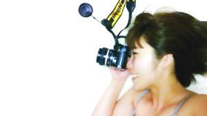 カメラを構えるおかっぱミユキの写真。風に吹かれながら、爽やかな笑顔を見せている。
