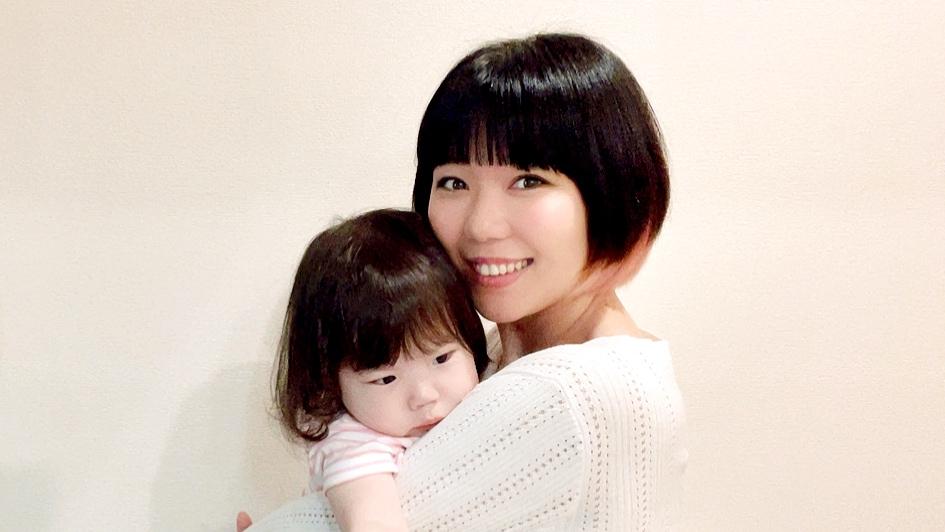 子供を抱っこしているおかっぱミユキの写真。 ピンク色のお洋服を着た子供が、抱っこされている。 母親は幸せそうに笑っている。