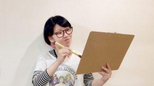 楽しそうに絵を描くおかっぱミユキ。左手にキャンバスを持って、筆で何かを描いている。