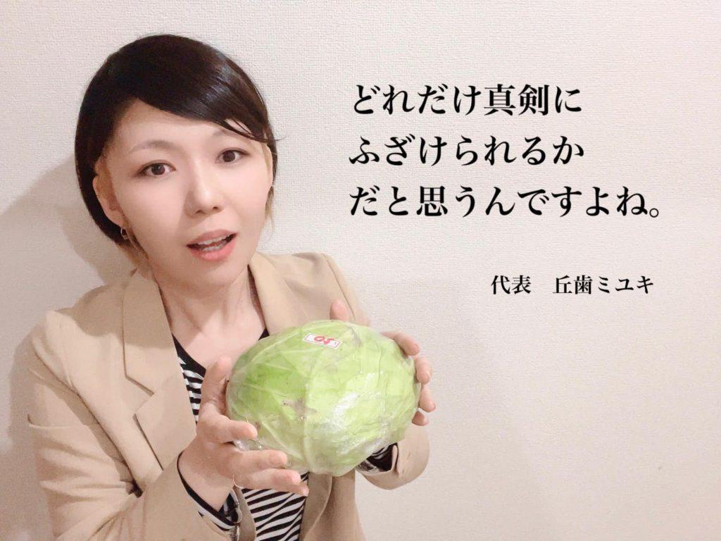 ふざけているおかっぱミユキの写真。インタビューを受ける社長の真似をして、手にはキャベツを持っている。