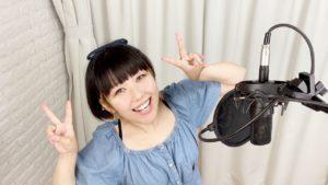 ボーカルレコーディング中のおかっぱミユキの写真。歌うのが楽しいようで、こちらを見てピースしながら笑っている。