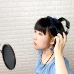 ボーカルレコーディング中のおかっぱミユキの写真。これから歌のレコーディングをするのか、ヘッドフォンを着けようとしている。